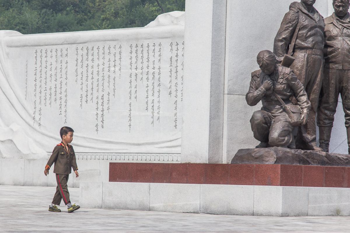Jongetje bij een monument ter nagedachtenis van de vaderland bevrijdingsoorlog