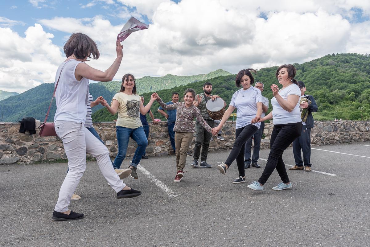 Lokale toeristen dansen net voordat ze een bezoek brengen aan het Gandzasar klooster